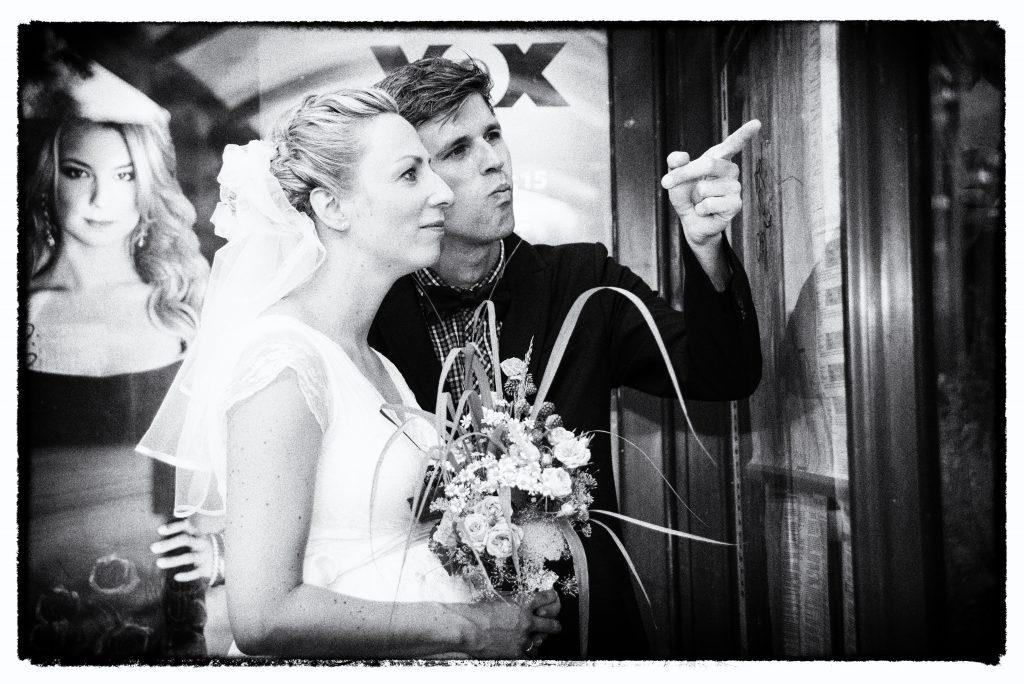 Hochzeitspaar an der Bushaltestelle mit Spiegelung in den Scheiben