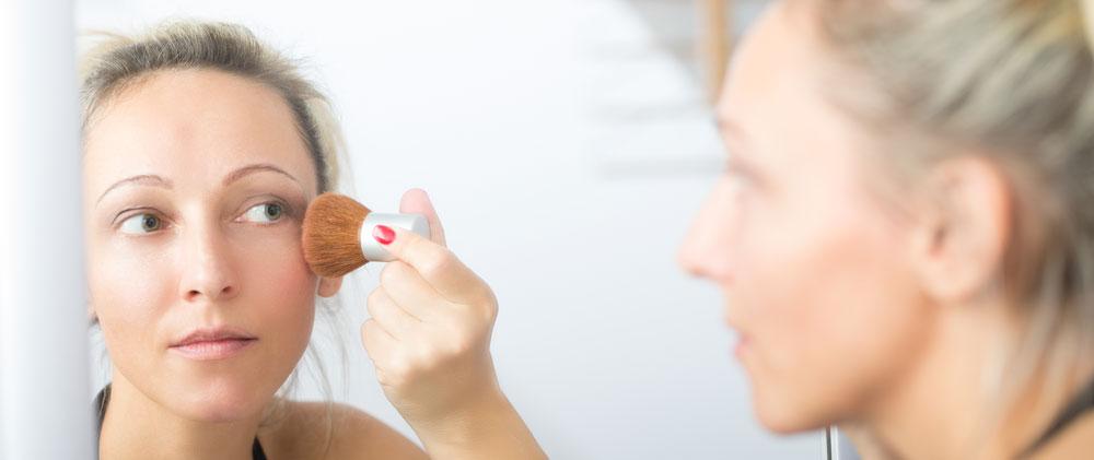 Foto Porträt Frau beim Pudern im Spiegel